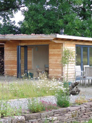 Larch Garden Room and Garden Store. The garden room is fully insulated and double glazed. It is heated with a wood burning stove and has a Sedum Living Roof.