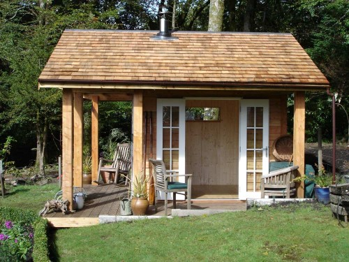 Larch Summer House, fully insulated and double glazed. With a Cedar shingle roof and wood burning stove.