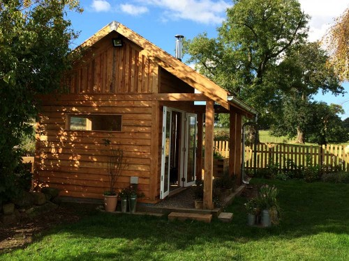 Larch Garden Studio, fully insulated and double glazed. It has a wood burning stove and is roofed in Cedar shingles.